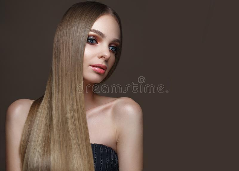Beautiful blond girl with a perfectly smooth hair, classic make-up and red lips. Beauty face royalty free stock photo