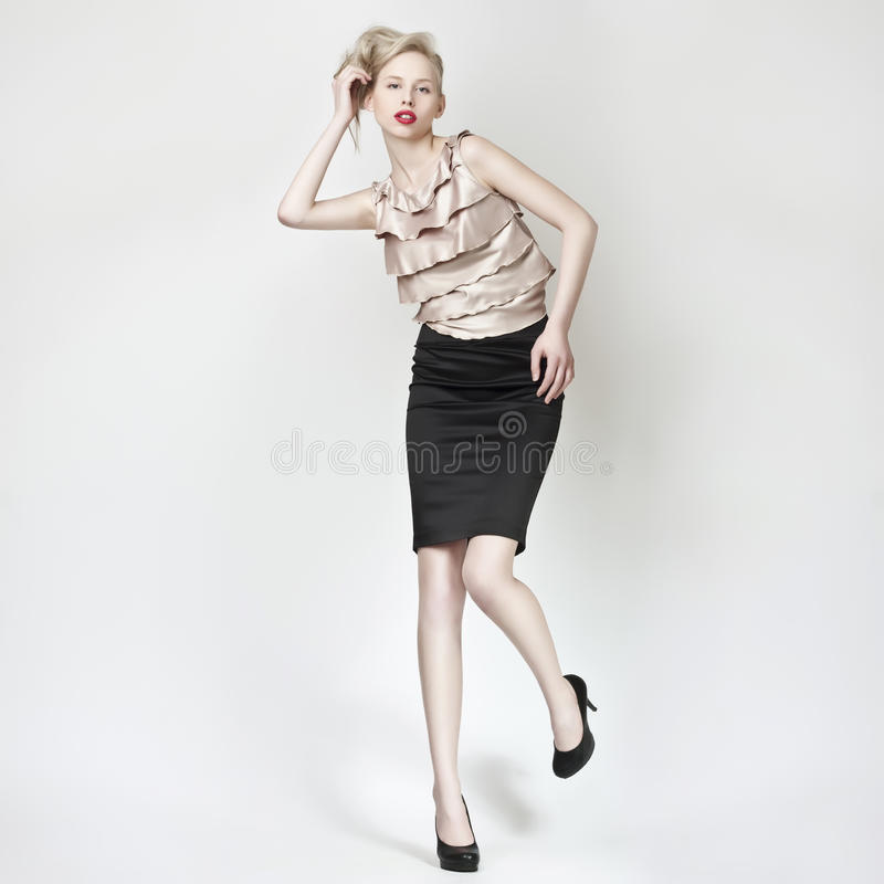 Beautiful blond girl pose in black mini skirt royalty free stock photo