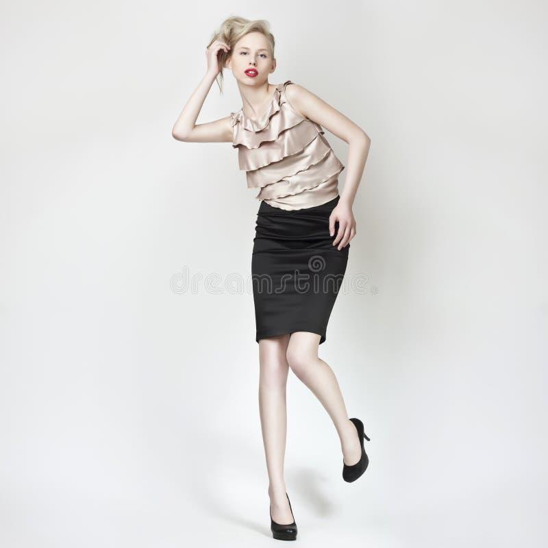 Beautiful blond girl pose in black mini skirt royalty free stock photo