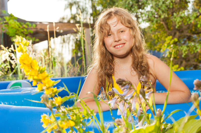 Beautiful blond girl posing in the swimming pool stock photos