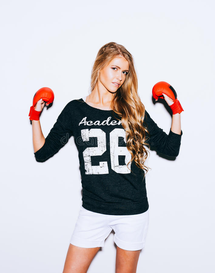 Beautiful blond girl in red boxing gloves posing on a white background. Lifted hands. Indoor. Warm color. stock photos