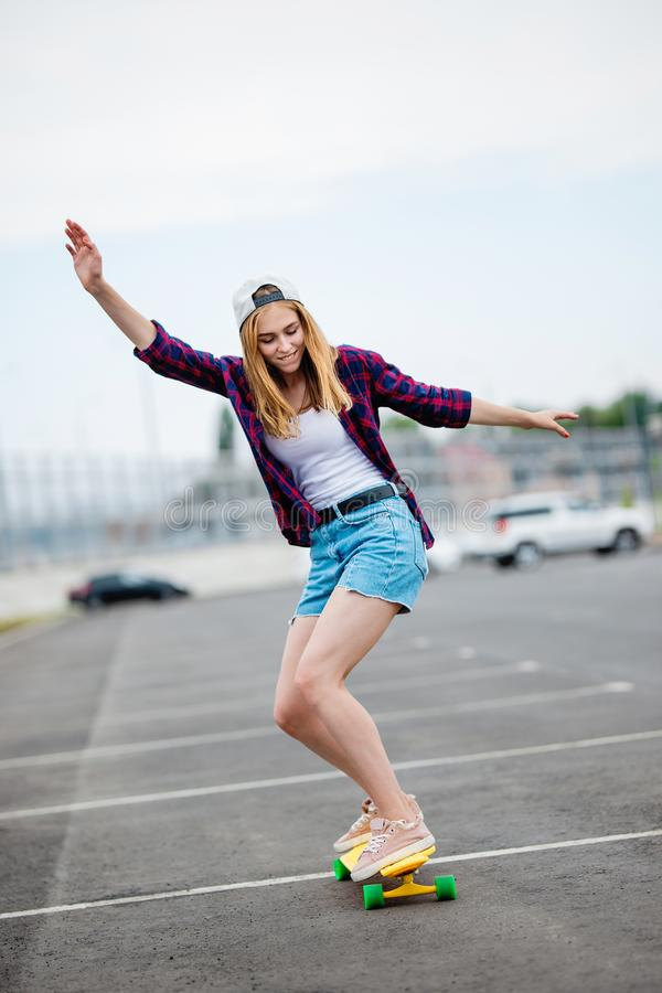 A beautiful blond girl wearing checkered shirt, cap and denim shorts is longboarding while stretching out her hands royalty free stock photo