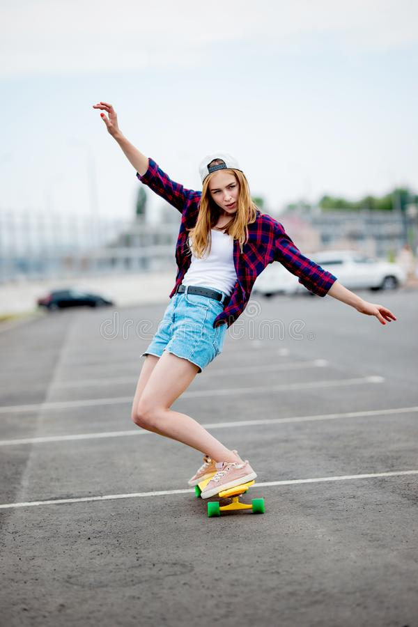 A beautiful blond girl wearing checkered shirt, cap and denim shorts is longboarding while stretching out her hands stock photos