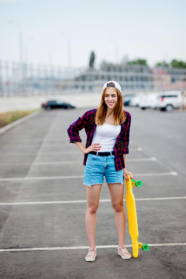 A beautiful blond girl wearing checkered shirt, cap and denim shorts is standing on the car park with a yellow longboard royalty free stock photography