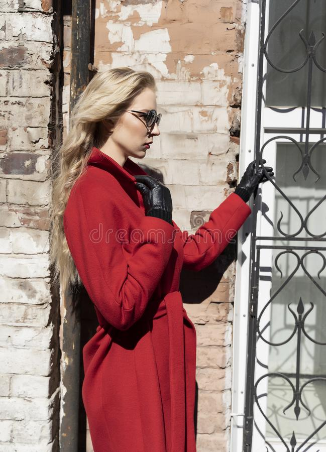 A beautiful blond girl wearing a red coat, sunglasses and gloves is standing against a brick wall illuminated by the bright sun. stock photos