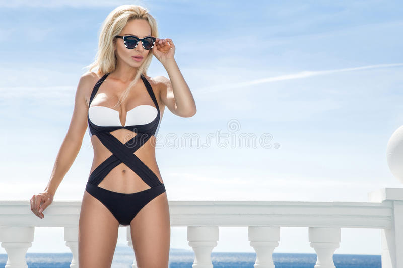 Beautiful blond hair woman young girl model in sunglasses and elegant white and black swimsuit royalty free stock image