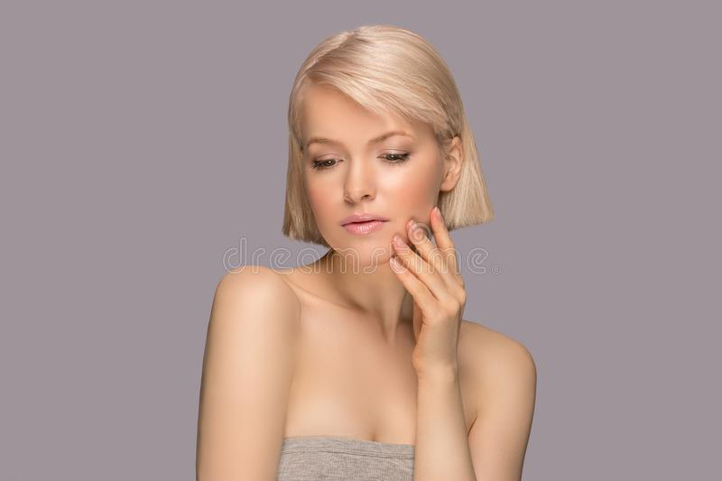 Beautiful blond hair woman. With perfect skin touching her face, gray background royalty free stock photos