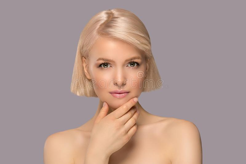 Beautiful blond hair woman. With perfect skin touching her face, gray background royalty free stock photography