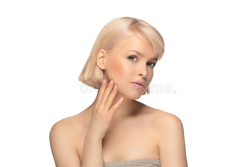 Beautiful blond hair woman. With perfect skin touching her face, isolated on white background stock photos