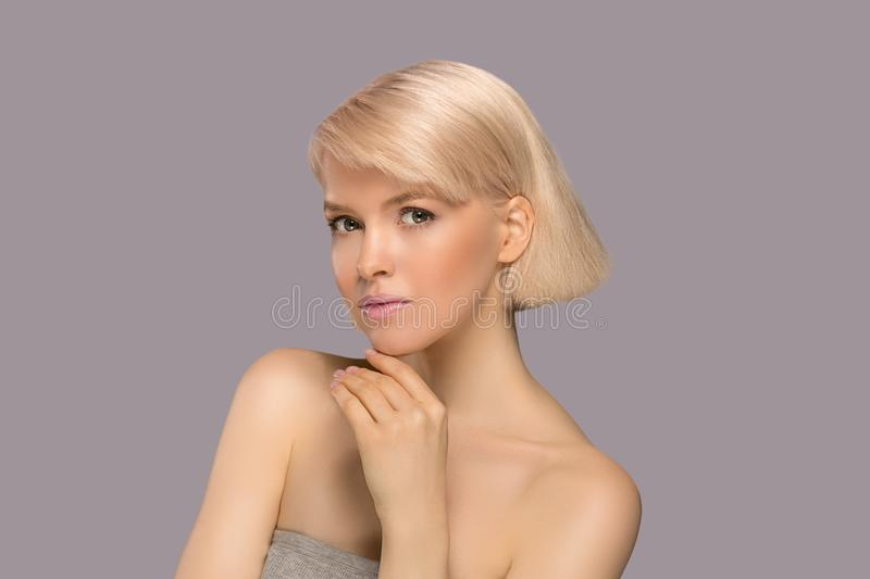 Beautiful blond hair woman. With perfect skin touching her face, gray background stock images