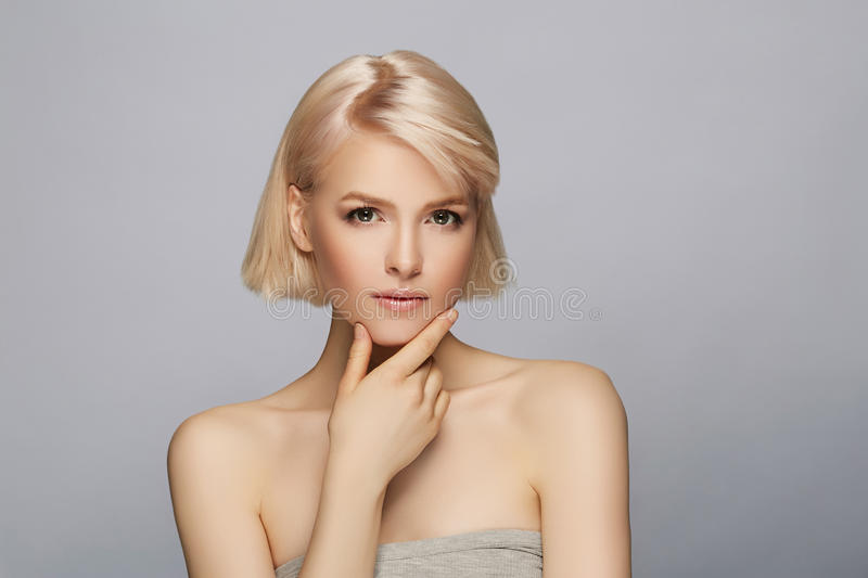 Beautiful blond hair woman. With perfect skin touching her face, gray background royalty free stock images