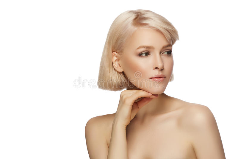Beautiful blond hair woman. With perfect skin touching her face, isolated on white background royalty free stock photos
