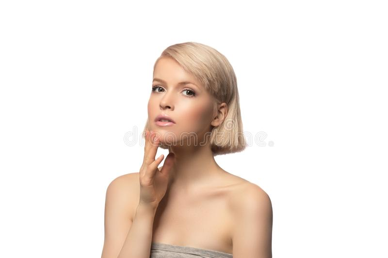 Beautiful blond hair woman. With perfect skin touching her face, isolated on white background royalty free stock photo