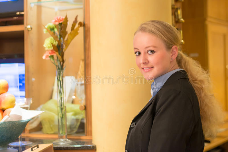 Beautiful blond hotel receptionist. Beautiful stylish blond hotel receptionist standing behind the service desk in a hotel lobby looking at the camera with a royalty free stock photo