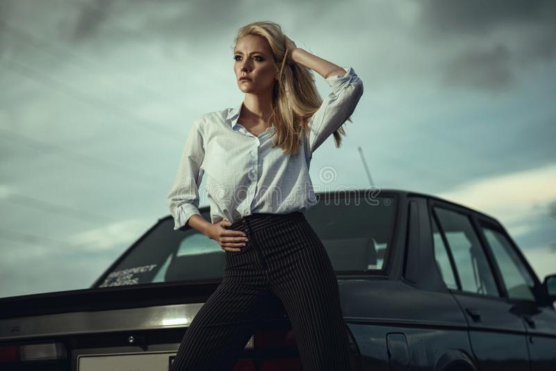 Beautiful blond lady in black striped high waisted pants and oversized white blouse standing at her old car looking away royalty free stock image