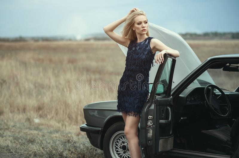 Beautiful blond lady in luxurious dark blue sequin tassel evening dress standing at her old car with open hood. Leaning on its door. Trying to catch a vehicle royalty free stock photos