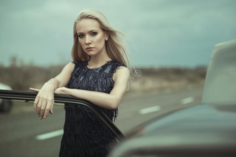 Beautiful blond lady in luxurious dark blue sequin tassel evening dress standing at her old car with open hood. Leaning on its door. Wind on her hair. Text royalty free stock photos