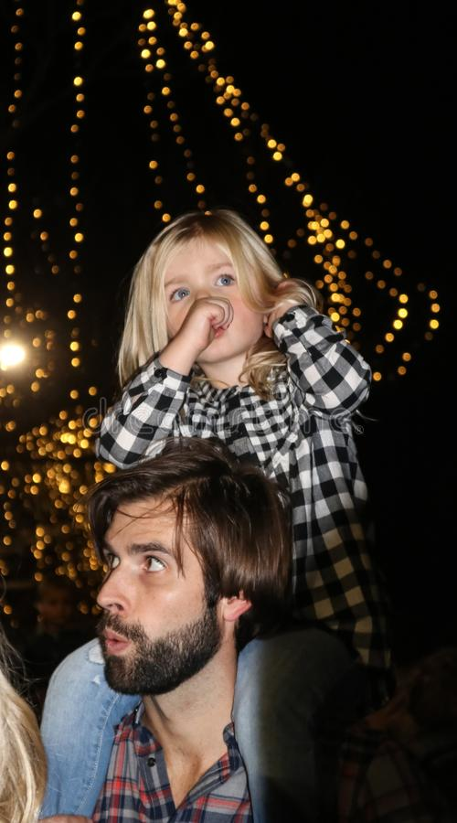 Beautiful blond little girl with her thumb in her mouth and a plaid shirt riding on her fathers shoulders with Christmas lights be stock image