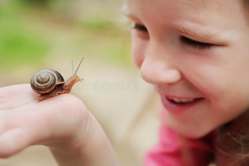 Little girl holding snails on her hand. Beautiful blond little girl watching and holding snails on her hand royalty free stock photography
