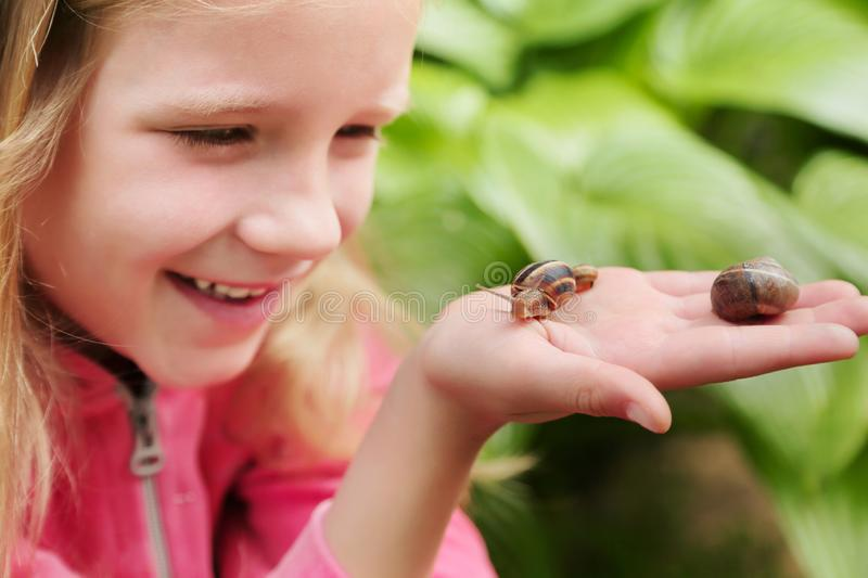 Little girl holding snails on her hand. Beautiful blond little girl watching and holding snails on her hand stock images