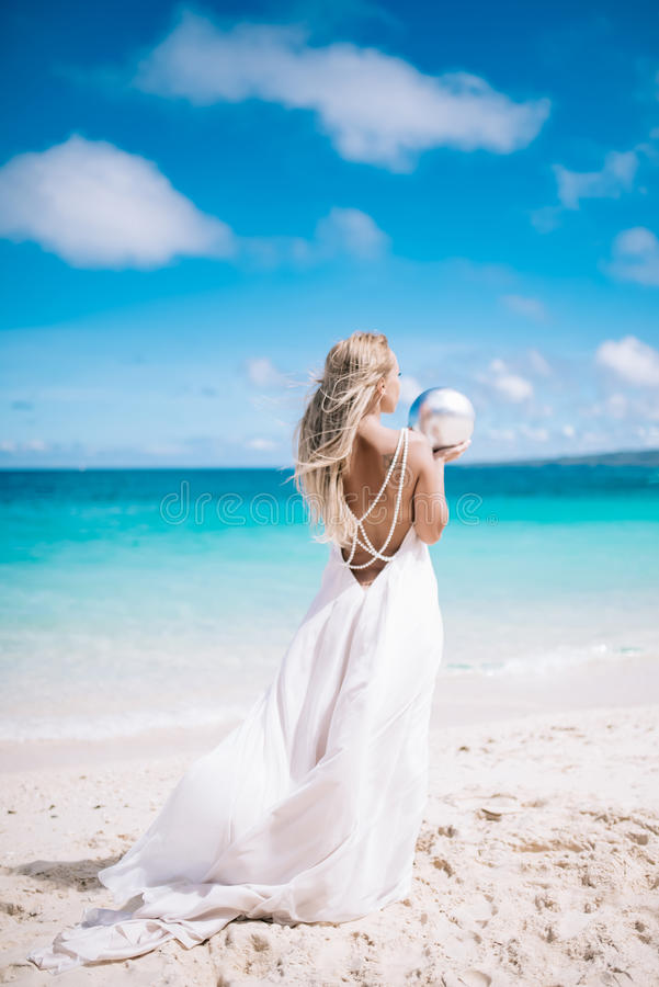 Beautiful blond long hair fiancee in a long white open back wedding dress stand on the white sand beach with a pearl. Looking to. The sea. Blue sky and royalty free stock photo