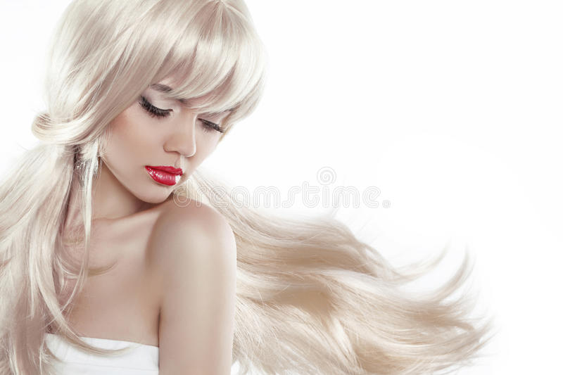 Beautiful blond with long hair. Makeup. Sensual woman with blowing hairstyle isolated on white background, posing at studio royalty free stock images