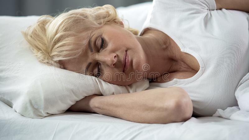 Beautiful blond mature lady lying in bed close-up, healthy sleep, retirement stock images