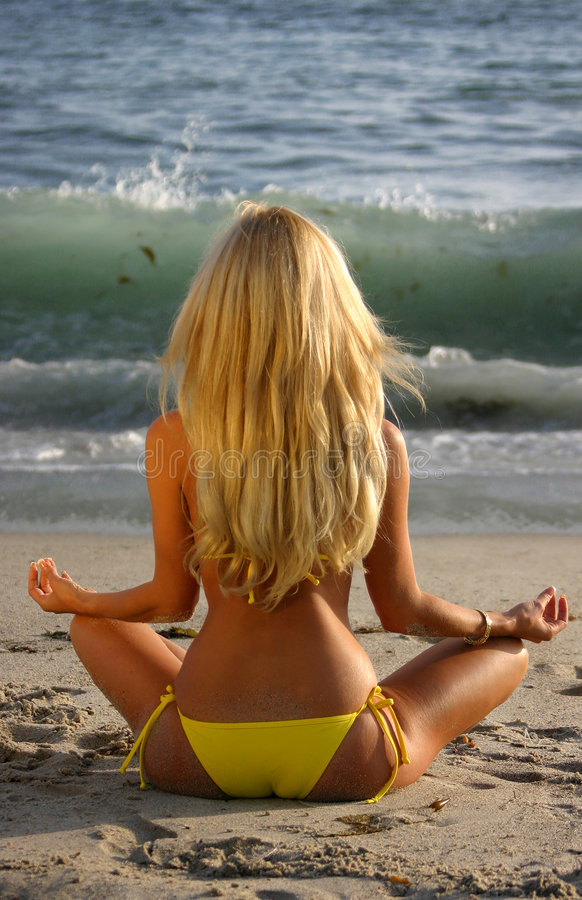 Beautiful Blond Meditating on the beach at Sunset. Beautiful Blond Meditating on the beach royalty free stock images