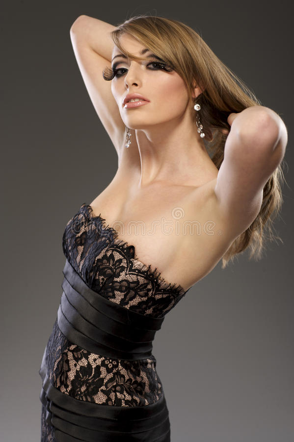 Beautiful blond model in black dress royalty free stock photography
