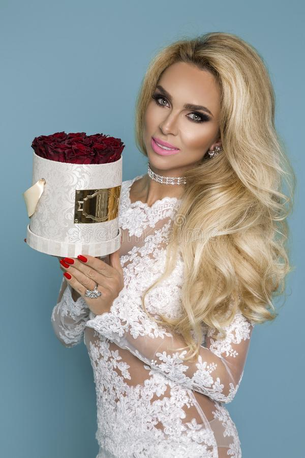 Beautiful blond model in elegant dress holding a bouquet of roses, flower box. Valentine`s and birthday gift on a blue background. Beautiful blond model woman in royalty free stock images