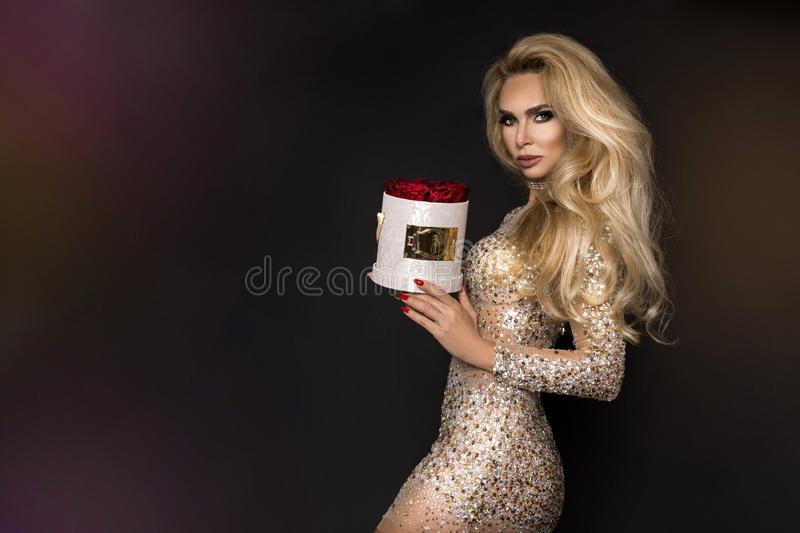 Beautiful blond model in elegant dress holding a gift, flower box with roses. Valentine`s gift. Beautiful blond model woman in elegant dress holding a gift stock photos