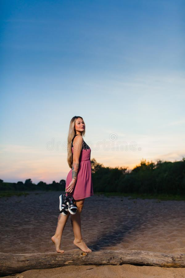 Beautiful blond model with long hair posing on the sand beach. At the background of summer sunset royalty free stock photography