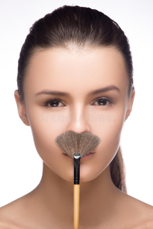 Beautiful blond model make a mustache with makeup brush. Head and shoulders, beauty studio shot isolated on white. fashion stock photos