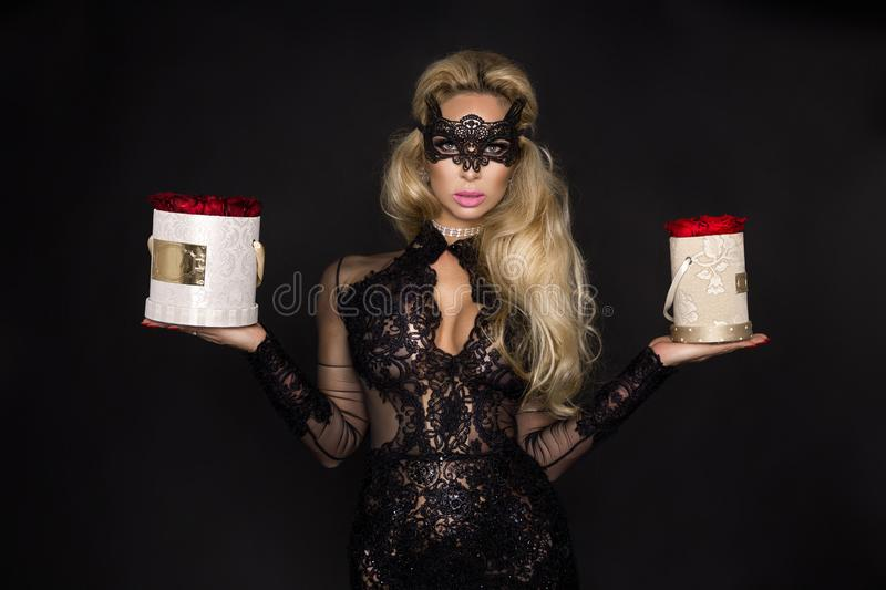 Beautiful blond model in elegant dress holding a gift, flower box with roses. Valentine`s gift royalty free stock photography