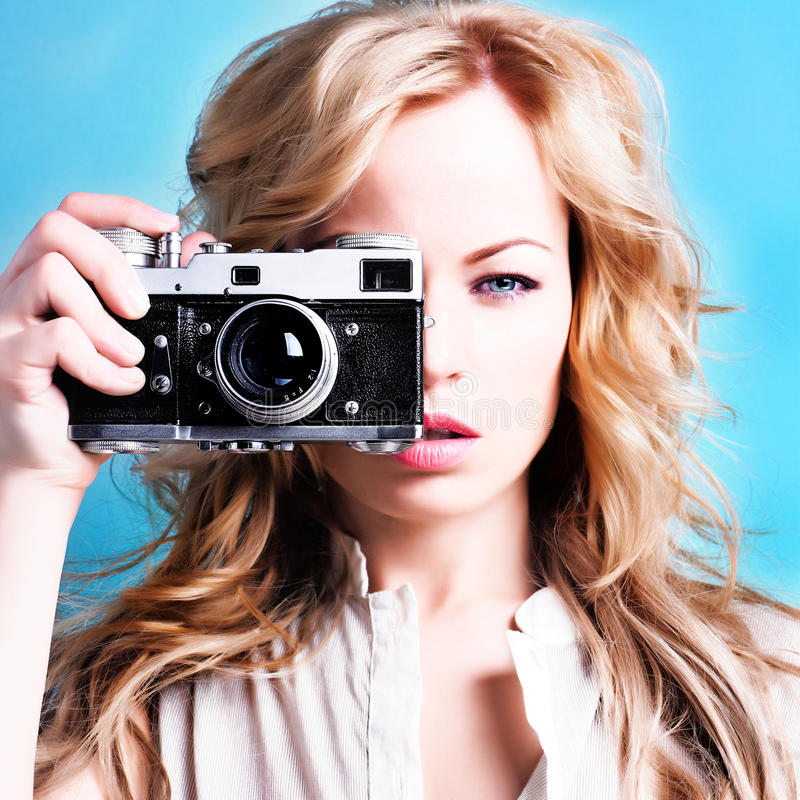 Beautiful blond photographer woman holding retro camera stock photography