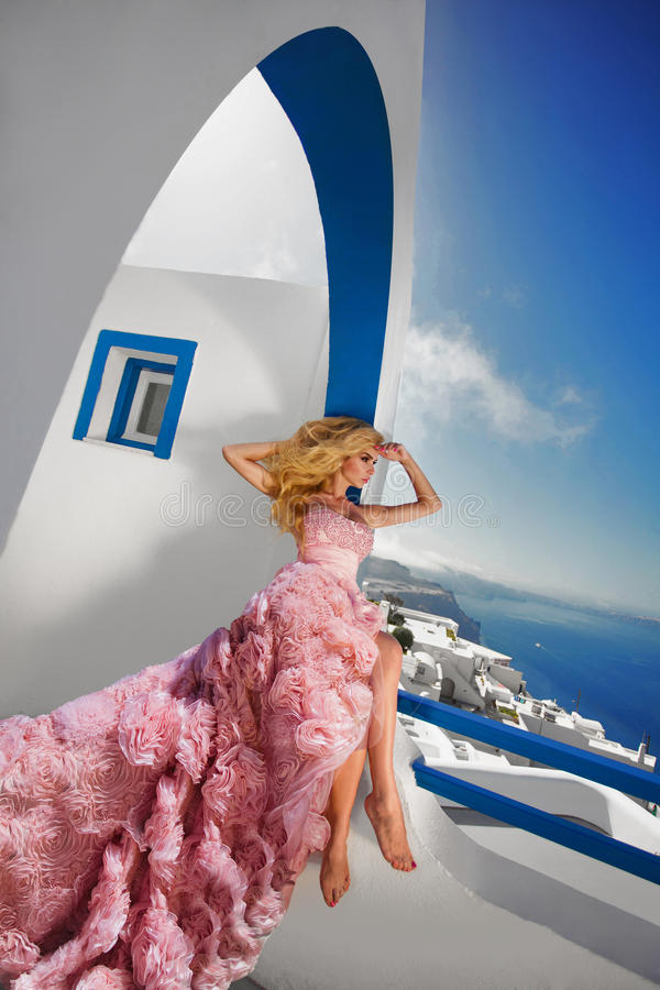 Free Beautiful Blond Runaway Bride In White Wedding Dress Fabulous With A Very Long Train Of Crystals In The Street On Santorini Stock Photo - 63538280