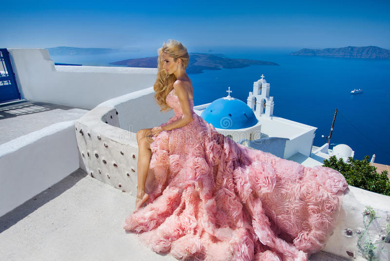 Beautiful blond runaway bride in white wedding dress fabulous with a very long train of crystals in the street on Santorini stock photo
