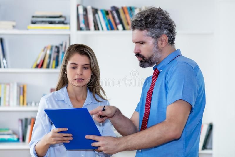 Beautiful blond secretary talking with middle-aged businessman stock photos