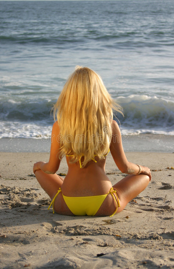 Beautiful Blond sitting on the beach. At Sunset looking at the Ocean stock photo