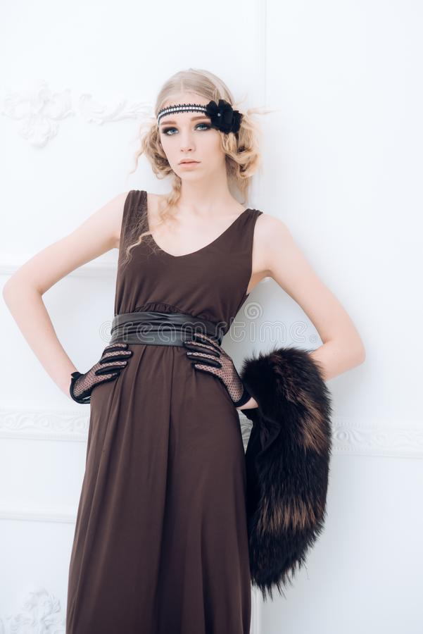Beautiful blond slim girl in 1920s dress and black fur collar isolated on white background stock images