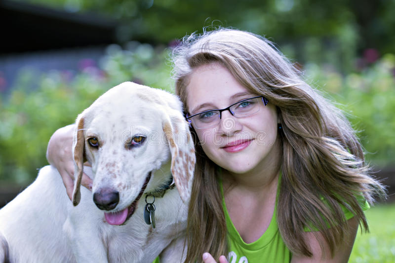 Beautiful blond teenager hugging dog. Beautiful blond teenager hugging white dog outdoors stock photo
