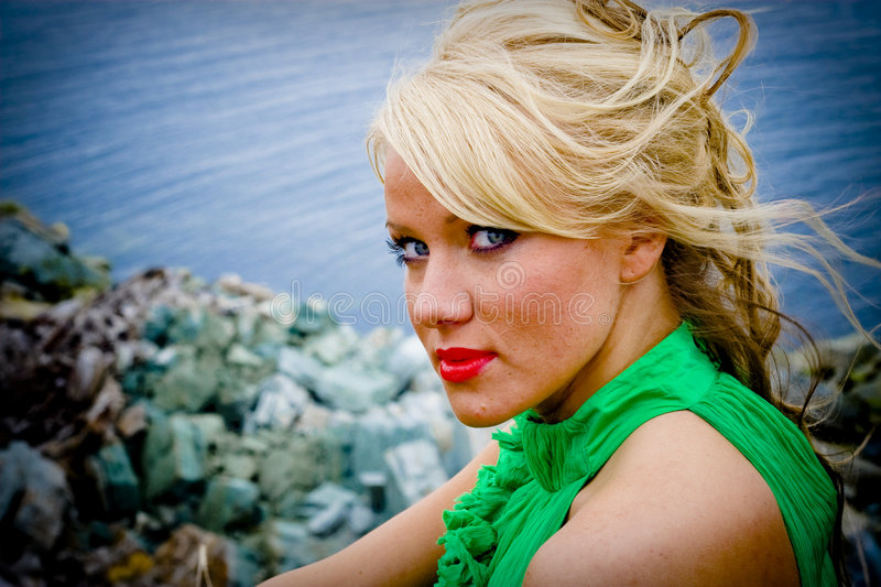 Beautiful Blond Woman. A portrait of a beautiful blond woman wearing a green dress, on the seaside royalty free stock images