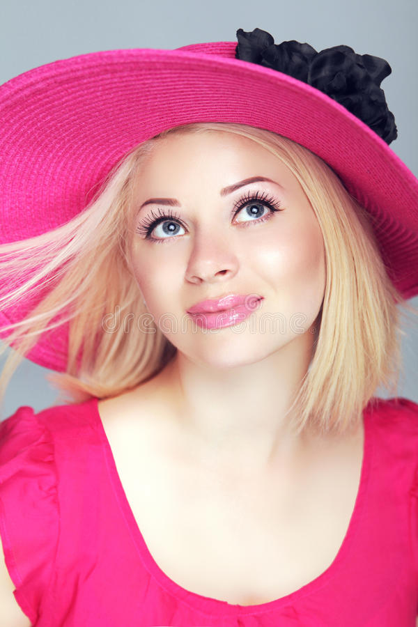 Beautiful blond woman with blowing hair in pink hat. Makeup, smiling girl posing at studio stock photos
