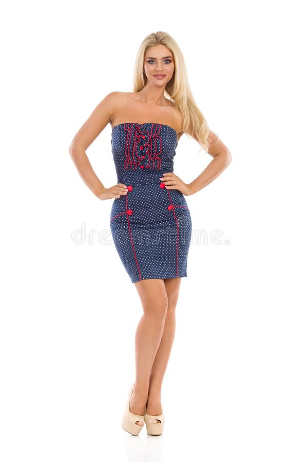 Beautiful Blond Woman In Blue Dotted Mini Dress And High Heels With Hands On Hip royalty free stock photo