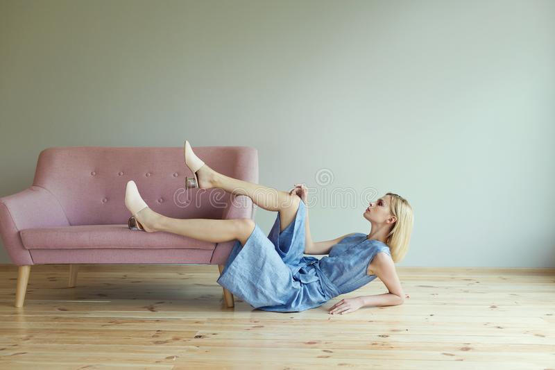 Beautiful blond woman in blue overalls in a light pink shoes sitting on a pink sofa. Fashion model. stock photography