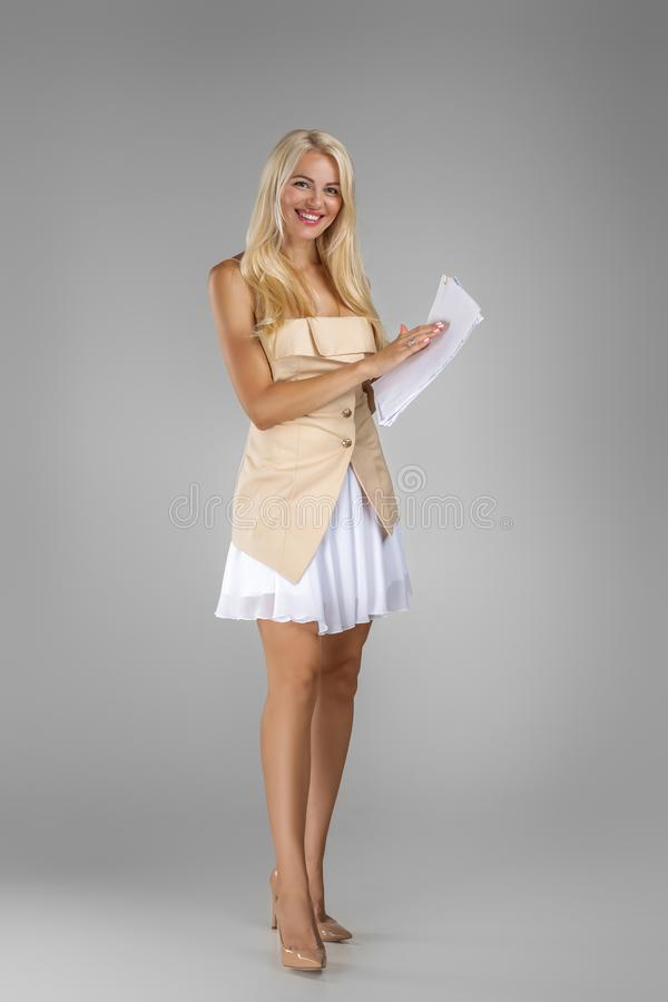 Beautiful blond woman in dress holding sheets documents royalty free stock images