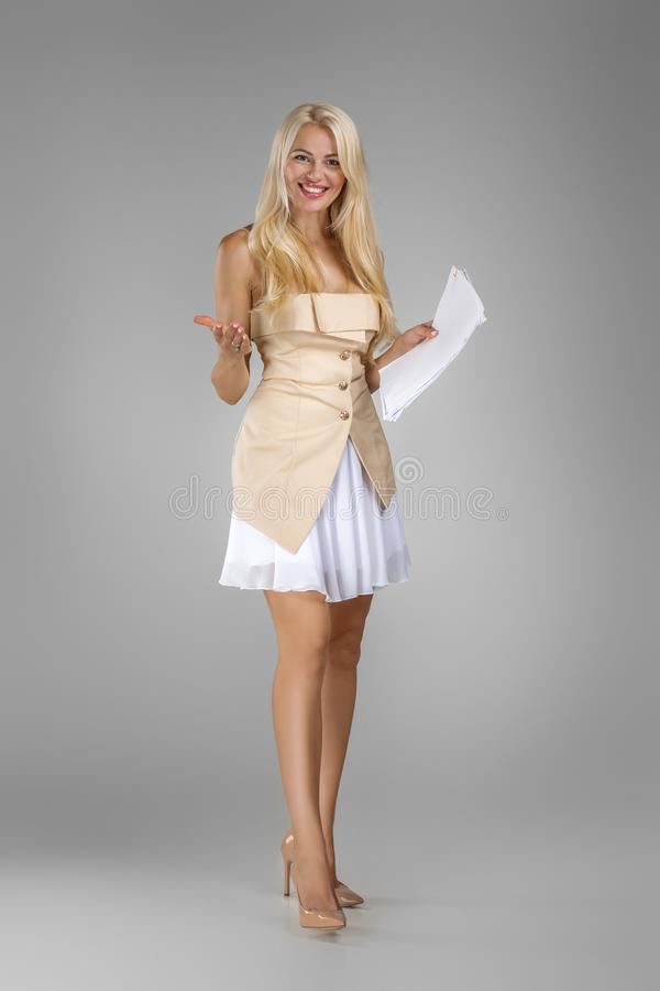Beautiful blond woman in dress holding sheets documents royalty free stock photo