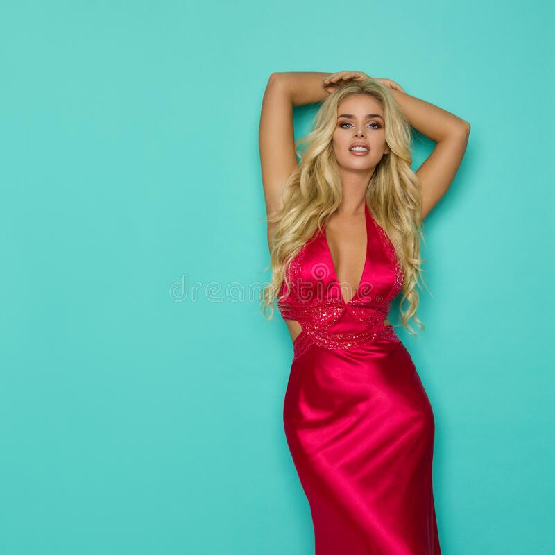 Beautiful Blond Woman In Elegant Red Dress Is Posing With Arms Crossed Behind Her Head. Sexy blond woman in elegant red dress is posing with arms crossed behind royalty free stock image