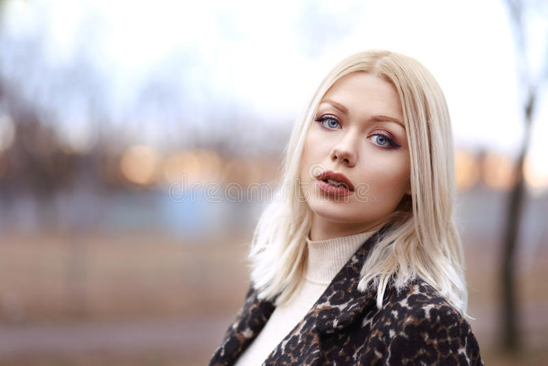 Beautiful blond woman. Half length portrait of young beautiful blond woman walking in the park in sunset royalty free stock photo
