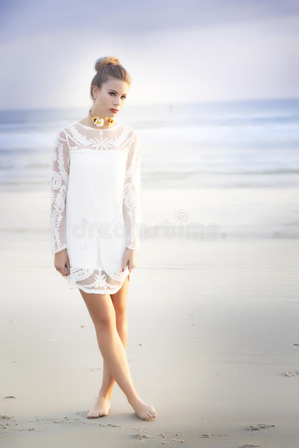 A beautiful blond woman with her hair in a bun with a short white lace dress standing on the beach. A beautiful blond woman with a bun in her hair and a floral royalty free stock photo